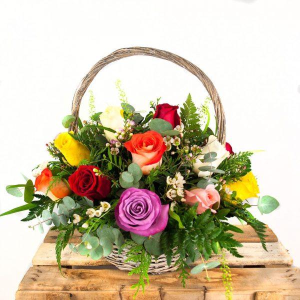 Cesta de flores compuesta por variedad de rosas de colores y algunos verdes decorativos a domicilio en Toledo.