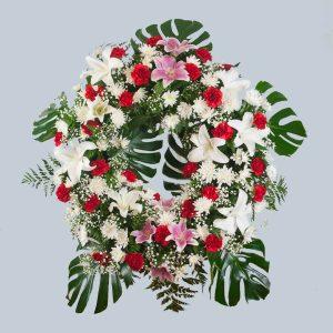Corona de flores en tono rojo y blanco decorada con hojas de monstera para enviar al tanatorio de Toledo o cualquier otro de la provincia.